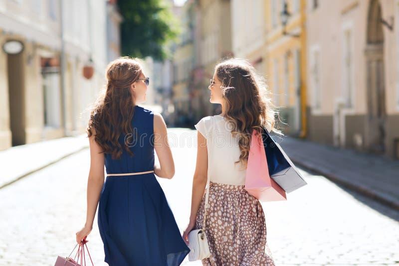 Gelukkige vrouwen die met het winkelen zakken in stad lopen royalty-vrije stock afbeelding