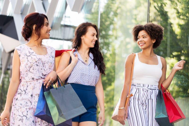 Gelukkige vrouwen die met het winkelen zakken in stad lopen royalty-vrije stock foto
