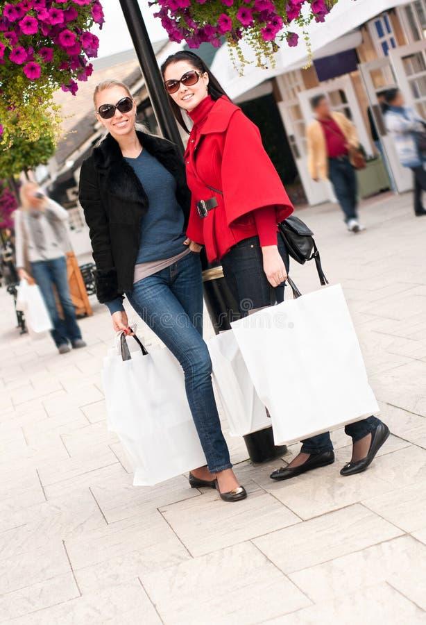 Gelukkige vrouwen die met witte zakken winkelen stock afbeeldingen