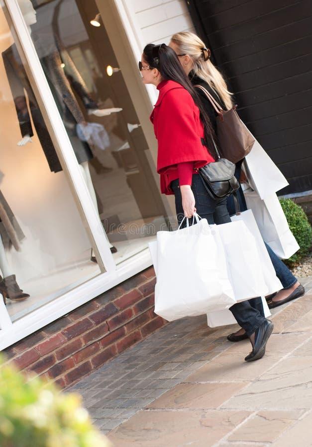 Gelukkige vrouwen die met witte zakken winkelen die de winkel bekijken royalty-vrije stock afbeelding