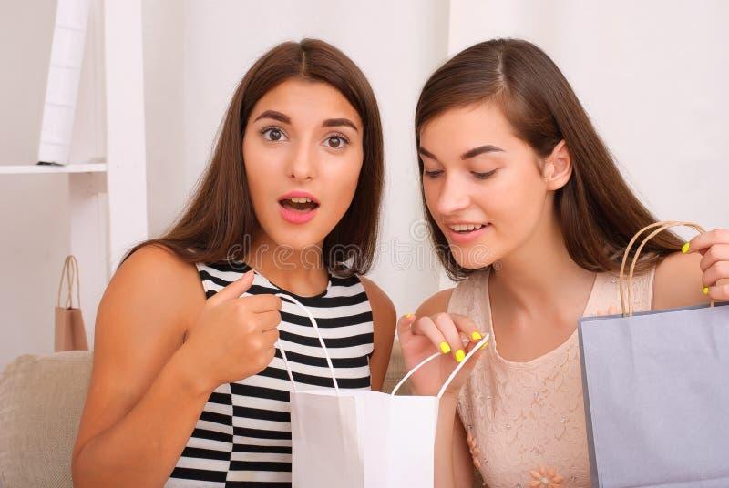 Gelukkige vrouwen die samen aankopen van het winkelen zakken kijken stock foto's
