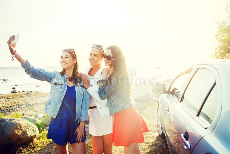 Gelukkige vrouwen die selfie dichtbij auto bij kust nemen stock afbeeldingen