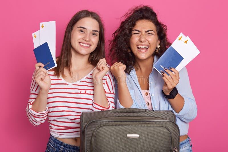 Gelukkige vrouwen die vuist zoals winnaars dichtklemmen, die paspoorten en instapkaartkaartje houden, die modieuze kleren, geïsol royalty-vrije stock afbeeldingen