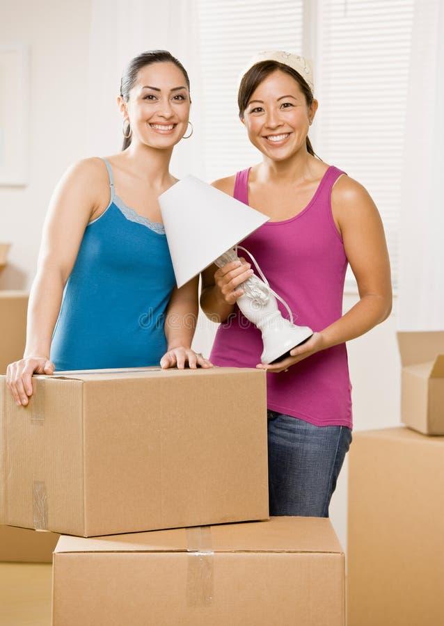 Gelukkige vrouwen die zich in nieuw huis bewegen stock foto