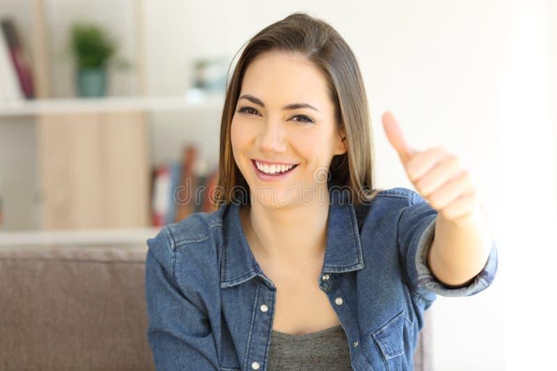 Gelukkige vrouwen gesturing duimen omhoog op een laag stock foto