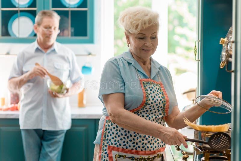 Gelukkige vrouwen kokende deegwaren stock fotografie