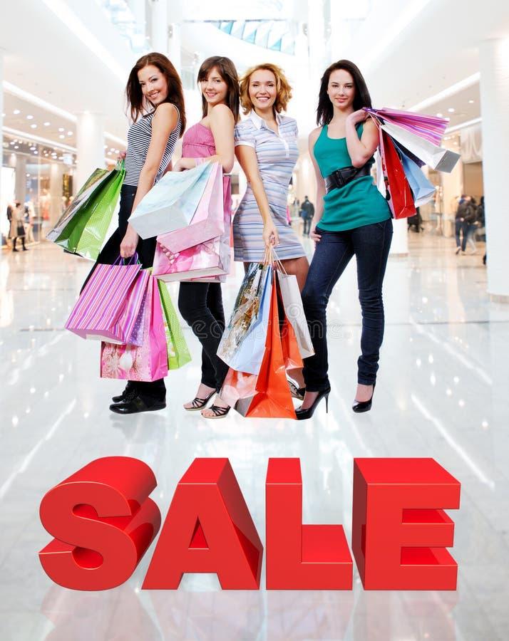 Gelukkige vrouwen met het winkelen zakken bij opslag stock foto