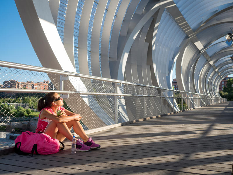 Gelukkige vrouwenagent die en een appel rusten eten op een moderne bridg royalty-vrije stock afbeeldingen