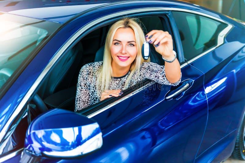 Gelukkige vrouwenbestuurder die autosleutels in haar auto houden stock foto's