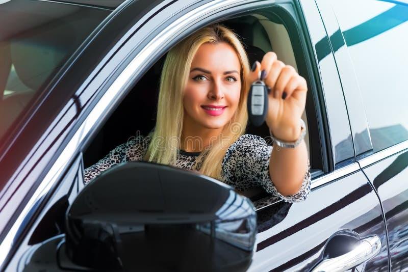 Gelukkige vrouwenbestuurder die autosleutels in haar auto houden stock afbeelding