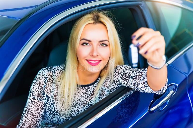 Gelukkige vrouwenbestuurder die autosleutels in haar auto houden royalty-vrije stock afbeeldingen