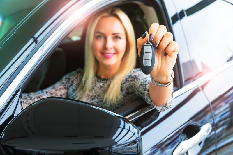 Gelukkige vrouwenbestuurder die autosleutels in haar auto houden stock foto