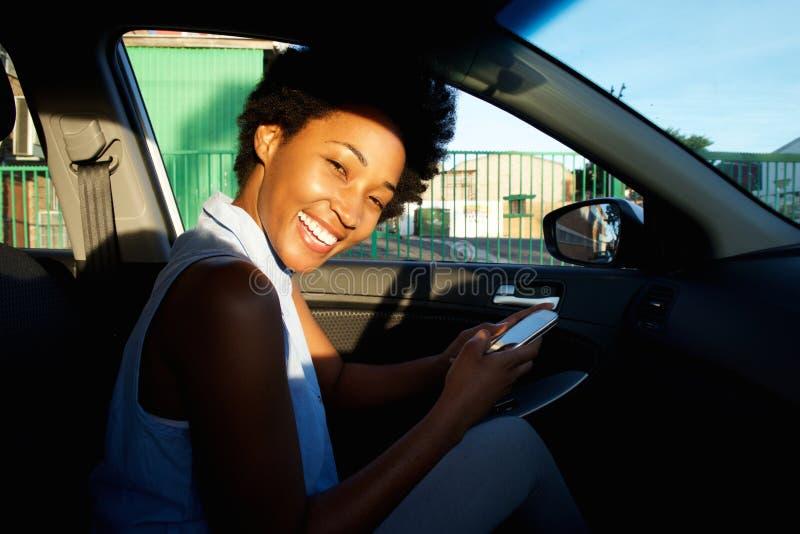 Gelukkige vrouwenbestuurder in een auto met mobiele telefoon royalty-vrije stock afbeelding
