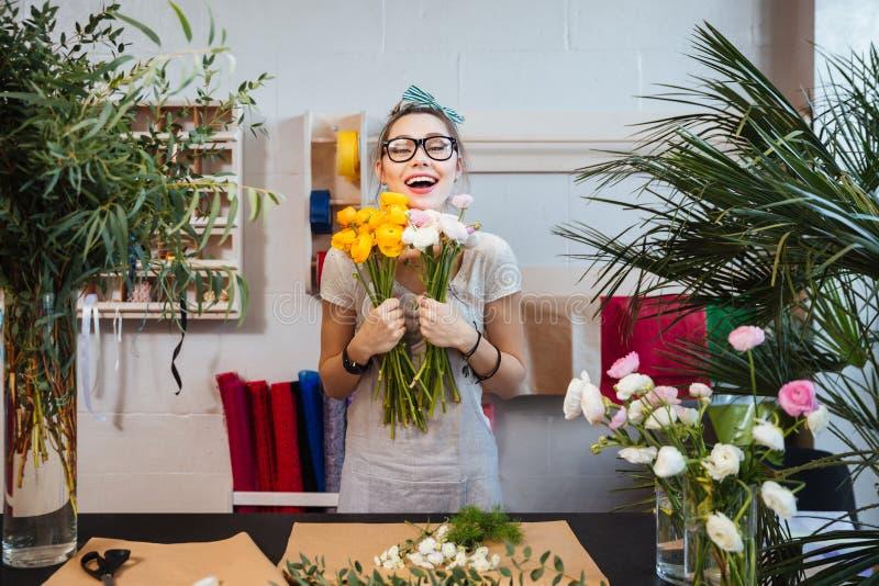 Gelukkige vrouwenbloemist met bos van en bloemen die bevinden zich lachen stock fotografie