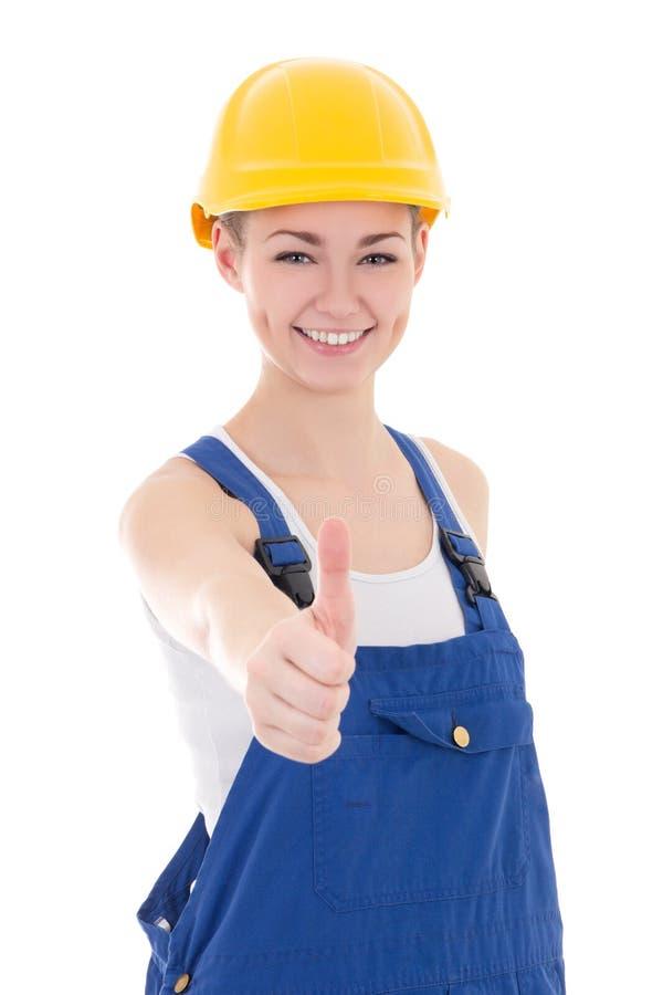 Gelukkige vrouwenbouwer in blauwe die overtrekkenduimen omhoog op whit wordt geïsoleerd stock foto's