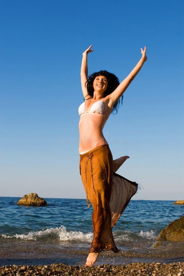 Gelukkige vrouwendans in het strand royalty-vrije stock fotografie
