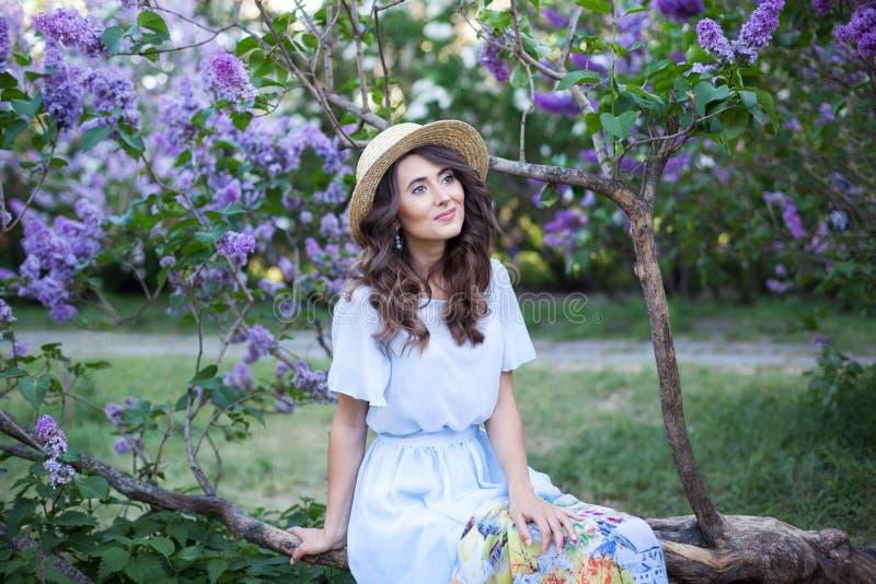 Gelukkige VrouwenLevensstijl, portret van een mooi meisje in een zitting van de strohoed dichtbij een tot bloei komende sering in royalty-vrije stock fotografie