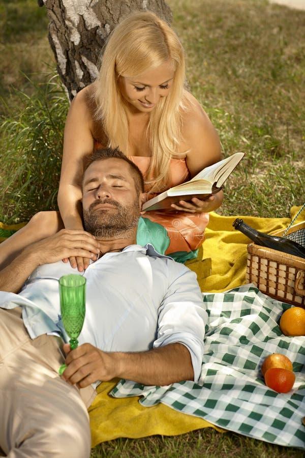 Gelukkige vrouwenlezing voor de knappe mens na picknick royalty-vrije stock foto