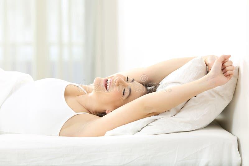 Gelukkige vrouwenontwaken het uitrekken zich wapens op een bed stock foto