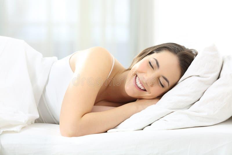 Gelukkige vrouwenslaap comfortabel in een bed stock foto