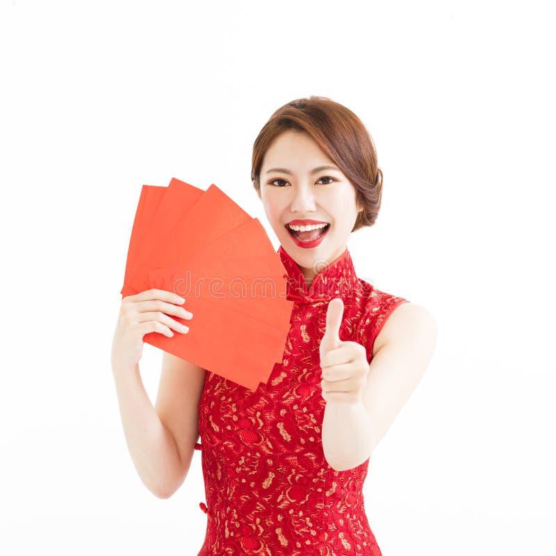 Gelukkige vrouwenslijtage cheongsam en tonend duim stock fotografie