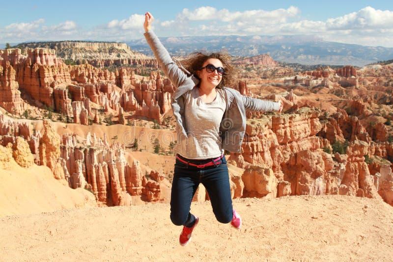 Gelukkige vrouwensprong in Bryce Canyon die en van mening genieten kijken stock fotografie