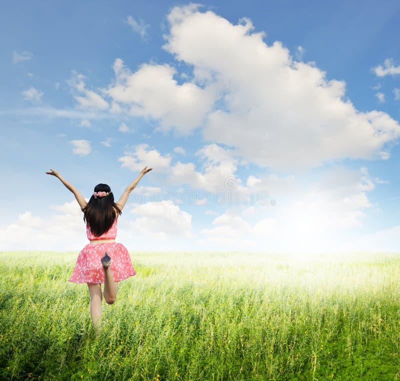 Gelukkige vrouwensprong in groene grasgebied en bule hemel royalty-vrije stock foto's