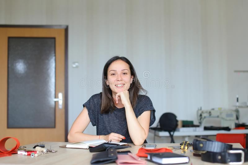 Gelukkige vrouwenzitting bij leeratelier en het maken van met de hand gemaakt notitieboekje, smartphone op lijst stock afbeelding