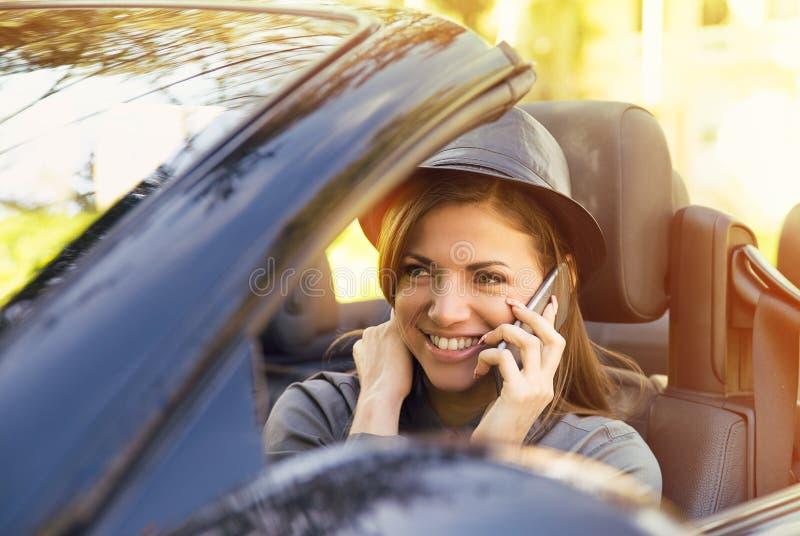 Gelukkige vrouwenzitting in convertibele nieuwe auto die op mobiele telefoon op een zonnige dag spreken royalty-vrije stock fotografie