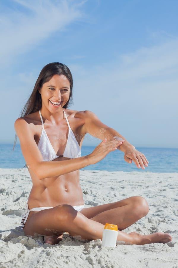 Gelukkige vrouwenzitting die op strand zonnescherm toepassen royalty-vrije stock fotografie