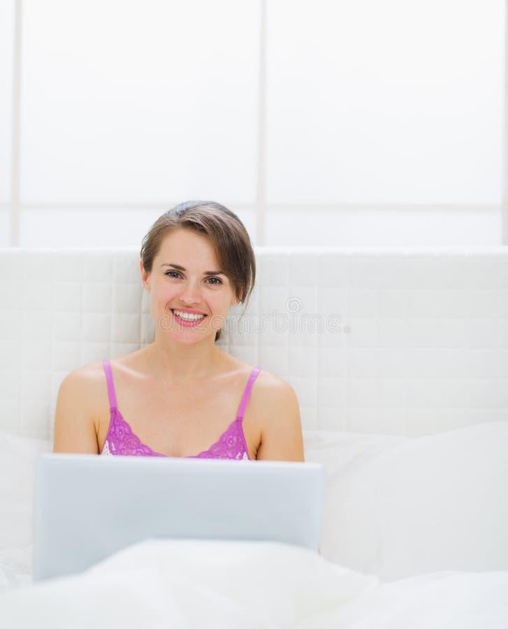Gelukkige vrouwenzitting op bed en het gebruiken van laptop stock foto's