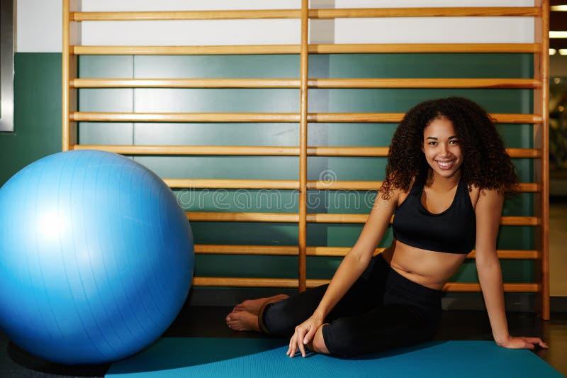 gelukkige vrouwenzitting op de mat die een rust na geschiktheid opleiding hebben bij gymnastiek royalty-vrije stock afbeelding