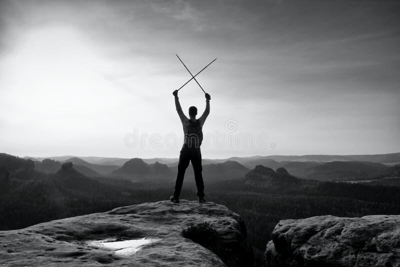 Gelukkige wandelaar met x gekruiste polen boven hoofd De mistige blaasbalg van de bergvallei Lange toeristenenthousiast royalty-vrije stock fotografie