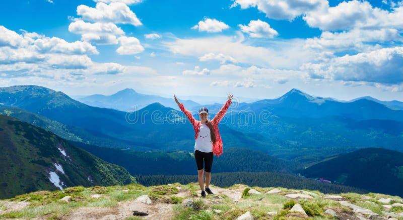 Gelukkige wandelaar met haar uitgestrekte wapens, vrijheid en geluk, voltooiing in bergen royalty-vrije stock fotografie
