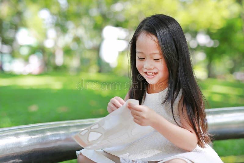Gelukkige weinig Aziatische kindmeisje het spelen stickers in het groene park stock foto's