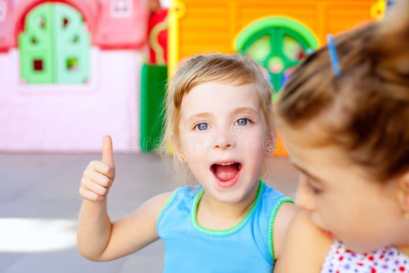 Gelukkige weinig zustermeisjes van kinderen met o.k. gebaar stock afbeeldingen