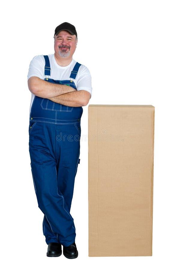 Gelukkige werkman die zich door grote kartondoos bevinden stock afbeelding