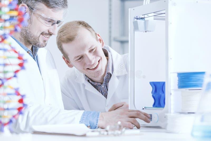 Gelukkige wetenschapper die bij laboratorium werken stock foto