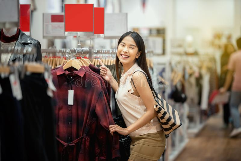 Gelukkige winkelende vrouw in winkelcentrum, die in klerenstor winkelen stock fotografie