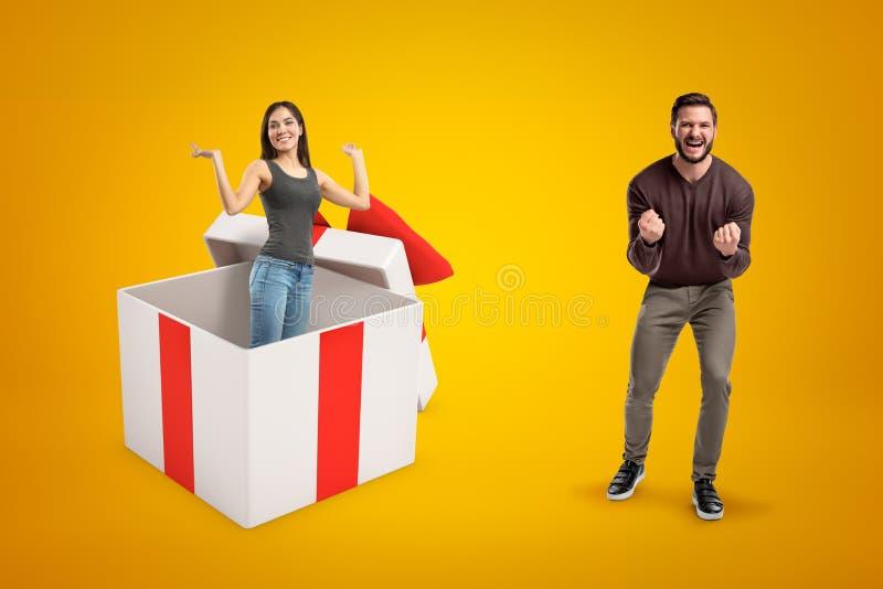 Gelukkige winnaarmens in vrijetijdskleding en meisje die jeans dragen en toevallige t-shirt binnen grote giftbox op gele achtergr stock afbeeldingen