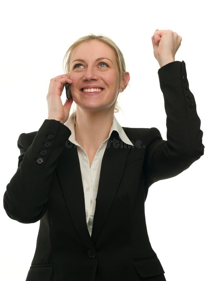 Gelukkige winnende onderneemster die op celtelefoon spreekt stock foto's