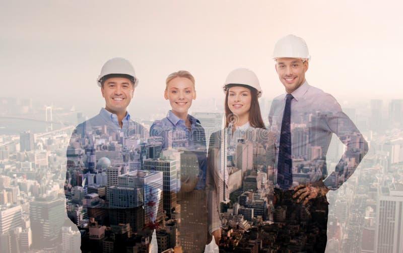 Gelukkige zakenlieden in helmen over stadsachtergrond royalty-vrije stock fotografie