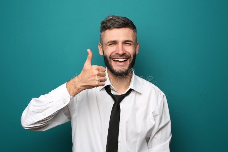 Gelukkige zakenman die duim-op gebaar op kleurenachtergrond tonen stock afbeelding