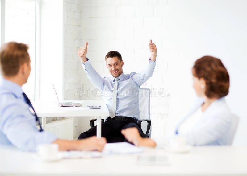 Gelukkige zakenman die duimen in bureau tonen stock fotografie