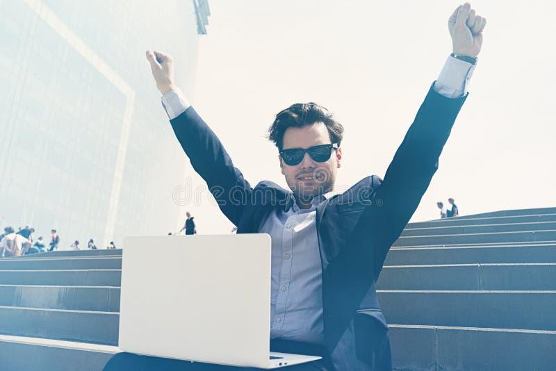 Gelukkige zakenman die kostuum dragen en moderne laptop in openlucht met behulp van Succesvolle bankier die buiten tijdens onderb stock afbeeldingen