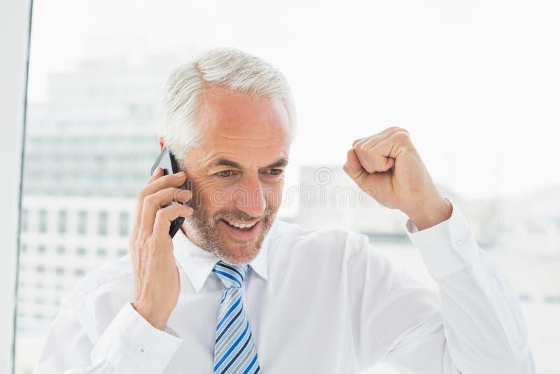 Gelukkige zakenman die mobiele telefoon in bureau met behulp van stock foto