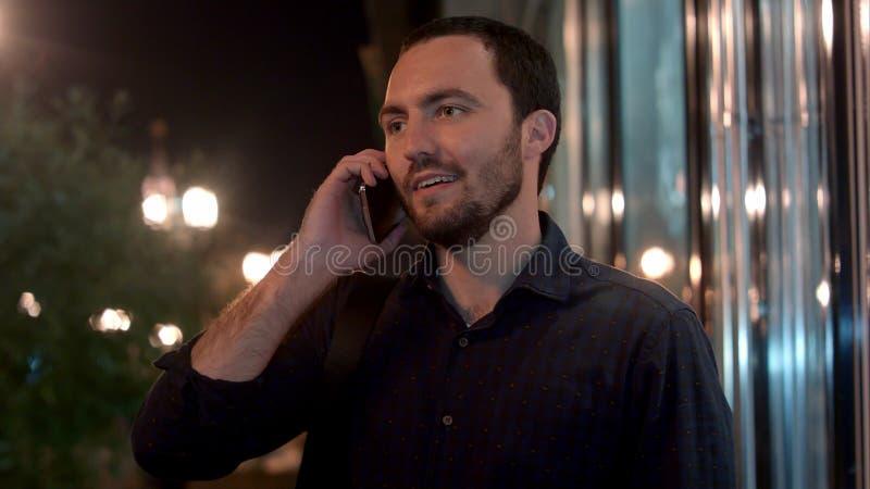Gelukkige zakenman die op de telefoon bij nachtstad spreken royalty-vrije stock foto