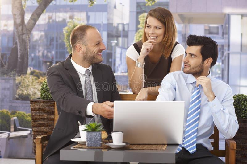 Gelukkige zakenman die project op laptop verklaren royalty-vrije stock afbeeldingen