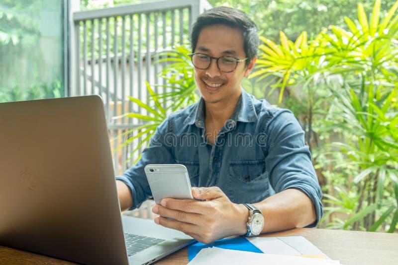 Gelukkige zakenman die terwijl het lezen van zijn smartphone met laptop op lijst glimlacht royalty-vrije stock foto's