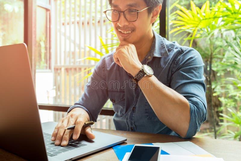 Gelukkige zakenman die terwijl het werken aan laptop glimlachen stock foto's
